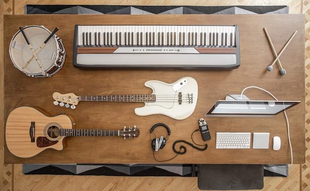Samenstelling van akoestische gitaar, basgitaar, muzikale toetsen, koptelefoon, sound mixer, snaredrum en computer op een bruine tafel in een muziekstudio.