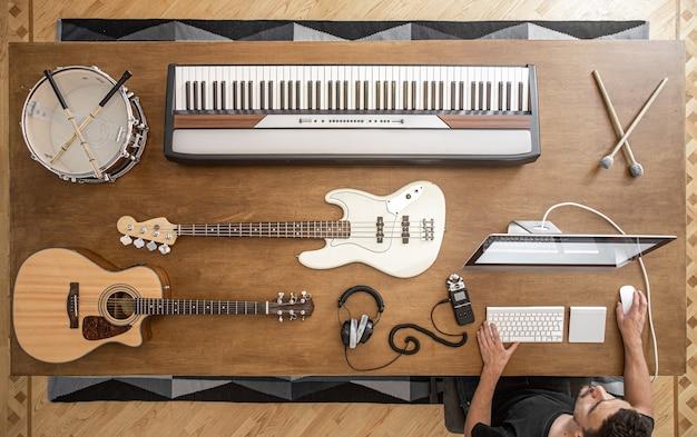 Samenstelling van akoestische gitaar, basgitaar, muzikale toetsen, koptelefoon, sound mixer, snaredrum en computer op een tafel in een muziekstudio.