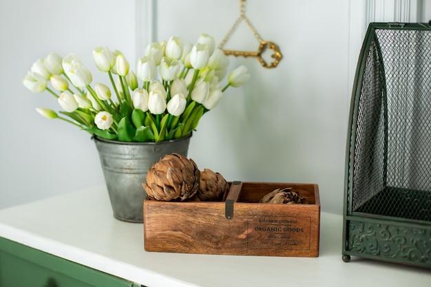 Samenstelling van artisjokbloemen in houten kist en boekettulpen in een vaas als zomerhuisdecoratie decor van droge bloemen thuis moederdag