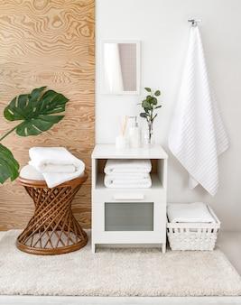 Samenstelling van badstofhanddoeken en badkameraccessoires in interieur. frisse en mooie badkamer met houten elementen, bloemen, monstera tropische bladeren en spiegel. vooraanzicht.