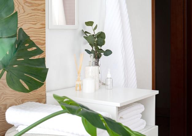 Samenstelling van badstofhanddoeken en badkameraccessoires in interieur. frisse en mooie badkamer met houten elementen, bloemen, monstera tropische bladeren en spiegel.