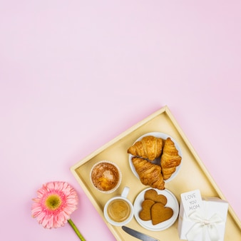 Samenstelling van bakkerij, beker en heden met tag op lade in de buurt van bloem