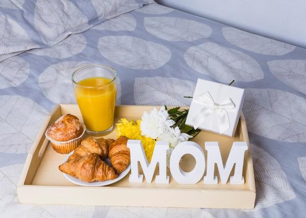 Samenstelling van bakkerij dichtbij glas, bloemen en mammawoord op dienblad op bed