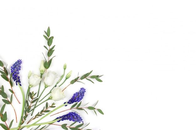 Samenstelling van bloemen. een patroon van rozen, greens en wilde bloemen op een witte achtergrond. plat lag, bovenaanzicht.