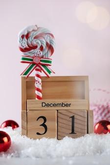 Samenstelling van blokkalender lolly en rode ballen in sneeuw nieuwjaar