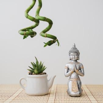 Samenstelling van boeddha en bloempot met bamboe hangende