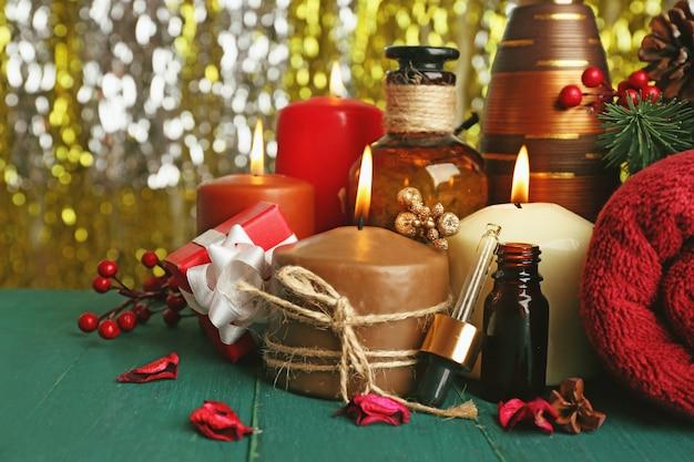 Samenstelling van brandende kaarsen, handdoek en aromaolie op groene houten tafel tegen fonkelende achtergrond