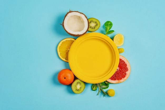 Samenstelling van citrusvruchten, sinaasappel en citroen, kokosnoot, kiwi op cyaanachtergrond