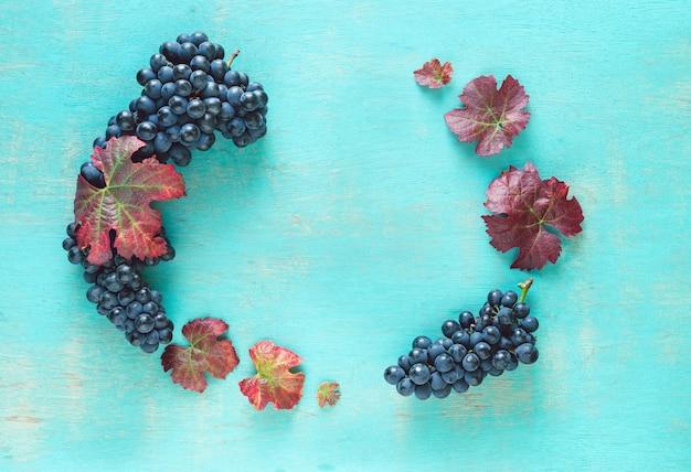 Samenstelling van clusters van rijpe zwarte druiven en wijnbladeren op een geschilderde blauwe achtergrond.