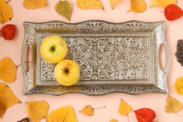 Samenstelling van de herfst met appels op metalen dienblad met herfstbladeren