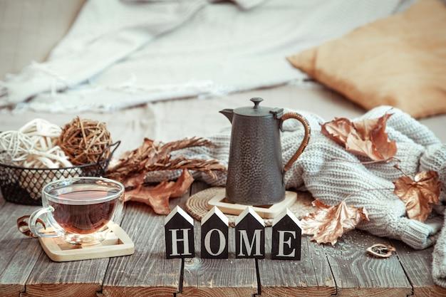 Samenstelling van de herfst met een kopje thee en houten woord huis.