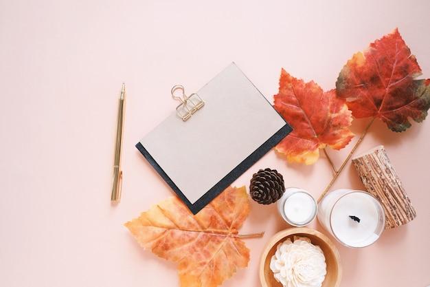Samenstelling van de herfst met kaars, bladeren en wenskaart