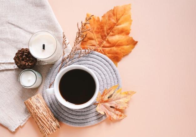 Samenstelling van de herfst met kaarsen, koffiekopje en bladeren