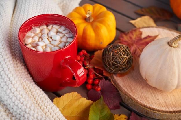 Samenstelling van de herfststemming op een houten tafel. rode kop koffie met marshmallows, verwarmend drankje. gezellige sfeer