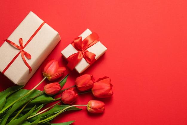 Samenstelling van de lente. boeket van rode tulpen en geschenkdoos op rode achtergrond.