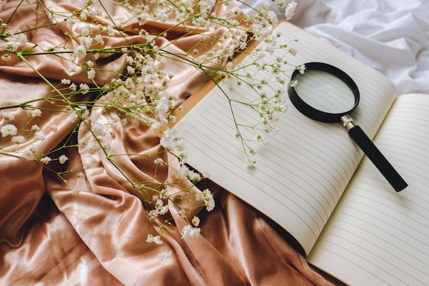 Samenstelling van de lente, witte gypsophila bloemen met notebook en vergrootglas op de gouden satijnen stof