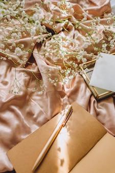 Samenstelling van de lente, witte gypsophila bloemen met notitieboekje en pen op de gouden satijnen stof