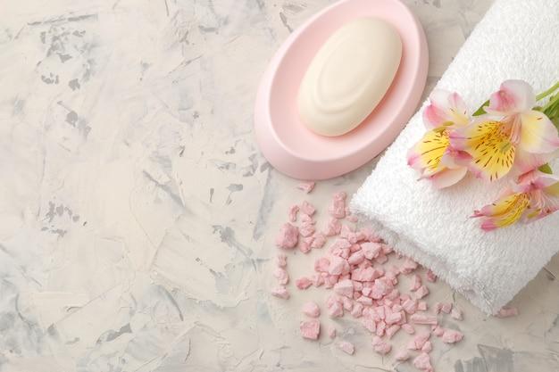 Samenstelling van de spa met een handdoek, zeezout en bloemen en zeep op grijs en wit betonnen bovenaanzicht met ruimte voor inscriptie