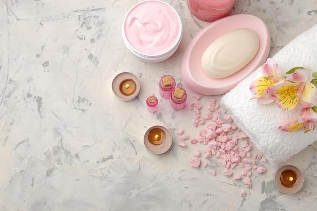 Samenstelling van de spa met zeezout, aroma-oliën, handdoeken en zeep en bodyscrubs op grijs en wit beton