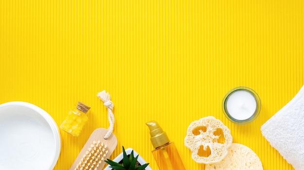 Samenstelling van dingen voor zelfzorg. sponzen, borstels, crèmes, flessen en kaarsen op gele achtergrond