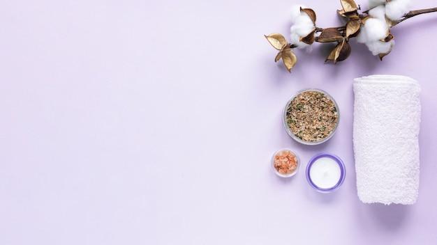 Samenstelling van dingen voor zelfzorg. zout, handdoek, kruiden en kaarsen op paarse achtergrond