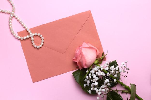 Samenstelling van een envelop, parel kralen en rozen op een roze achtergrond