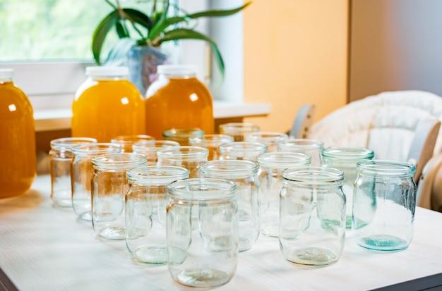 Samenstelling van een groot aantal potten en drie potten honing op een witte tafel tegen een achtergrond van licht