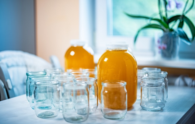 Samenstelling van een groot aantal transparante lege glazen potten en drie grote glazen transparante potten met gele zoete honing, staande op een grote witte tafel tegen een achtergrond van fel zonlicht