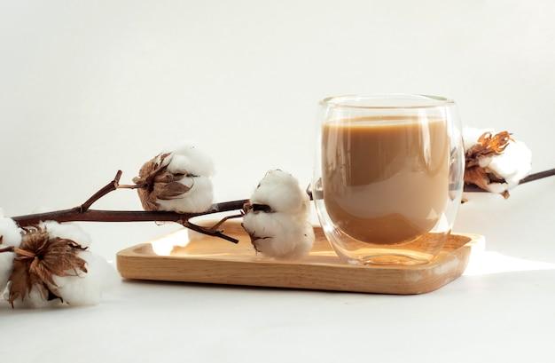 Samenstelling van een kopje koffie met melk in dubbel glas en een tak van katoenen bloemen op houten plaat