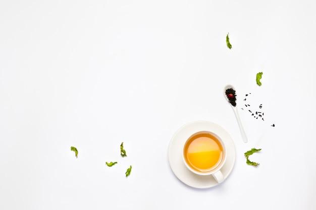 Samenstelling van een kopje thee, groene thee, zwarte thee, keramische lepel met thee