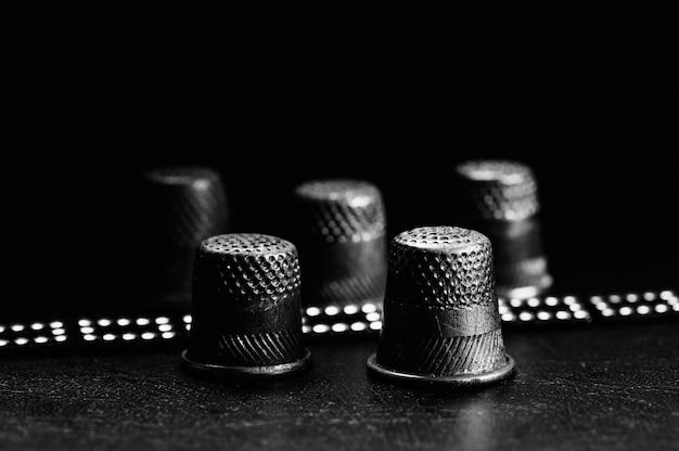 Samenstelling van enkele oude vingerhoedjes op zwart oppervlak in macro