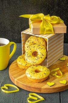 Samenstelling van feestelijke ontbijtthee en donuts op een houten ondergrond in gele kleuren