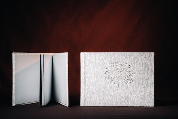 Samenstelling van fotoboeken in natuurlijk wit leer van verschillende formaten. het witboek op een donkere achtergrond.