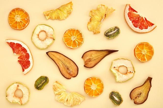 Samenstelling van gedroogde vruchten (kiwi, peer, mandarijn, sinaasappel, grapefruit, appel) op gekleurd. gedroogd fruit bovenaanzicht