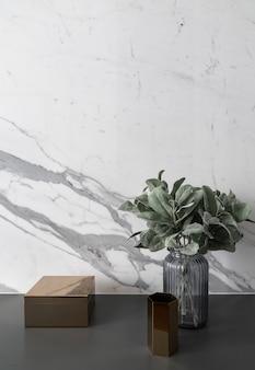 Samenstelling van gouden hexagon en rechthoekige roestvrijstalen doos met kunstmatige plant in glazen vaas op grijze gespoten werktafel met marmeren muur
