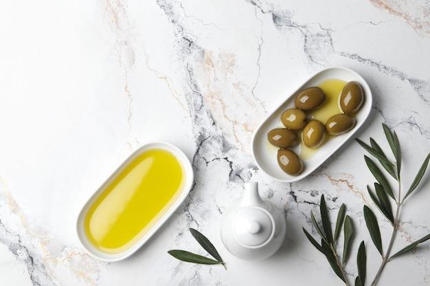 Samenstelling van groene olijven in olie, kruiden, olijftak, juskom op een marmeren achtergrond. ruimte voor tekst.