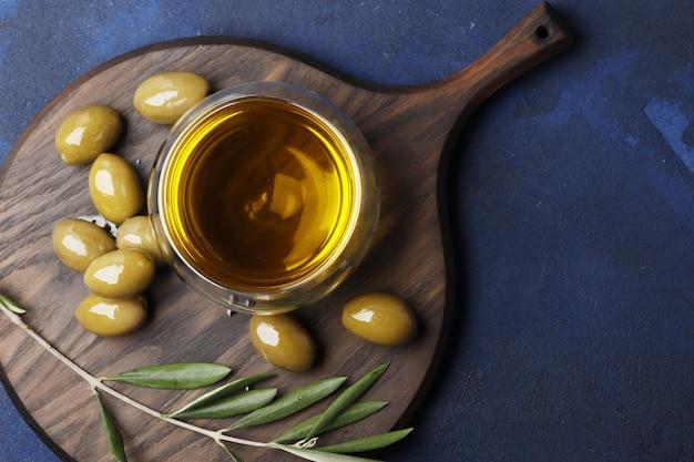 Samenstelling van groene olijven, olie, kruiden op een blauwe achtergrond. ruimte voor tekst.
