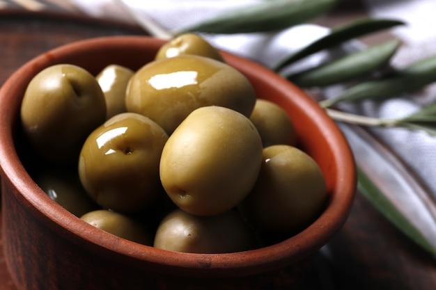 Samenstelling van groene olijven; olijfolie; marinade op een houten achtergrond close-up