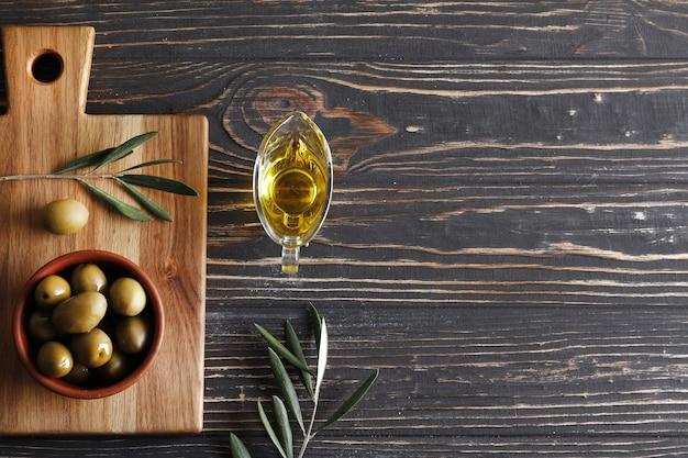 Samenstelling van groene olijven, olijfolie, op een houten ondergrond met ruimte voor tekst.