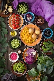 Samenstelling van het voedsel. biologisch voedsel, groenten en granen in veelkleurige kleikommen op een houten tafel.