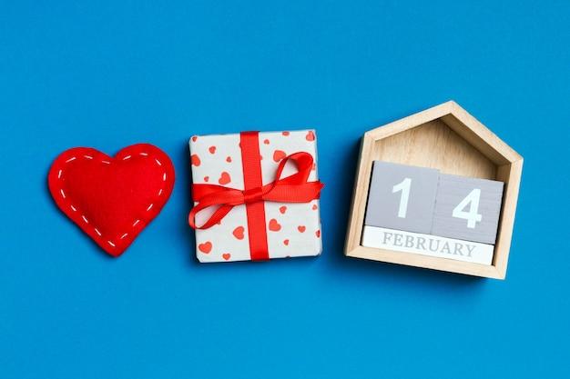 Samenstelling van houten kalender, vakantie witte geschenkdozen en rode textiel harten op kleurrijke achtergrond. de veertiende februari. valentijnsdag concept