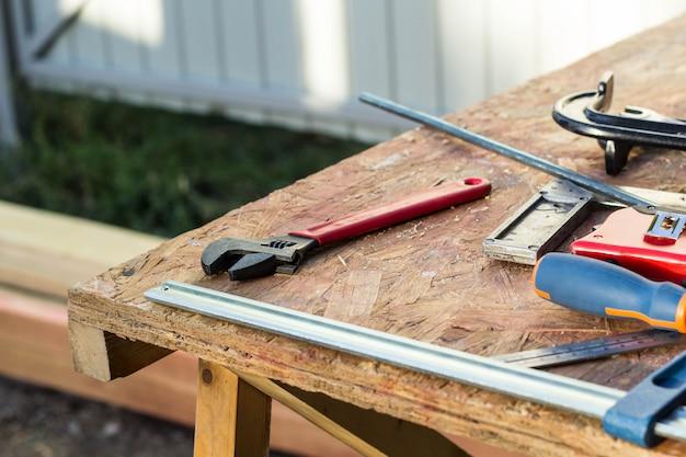 Samenstelling van hulpmiddelen van de bouw op een oude houten tafel van tangen, pijptang, schroevendraaier, klemmen, roulette