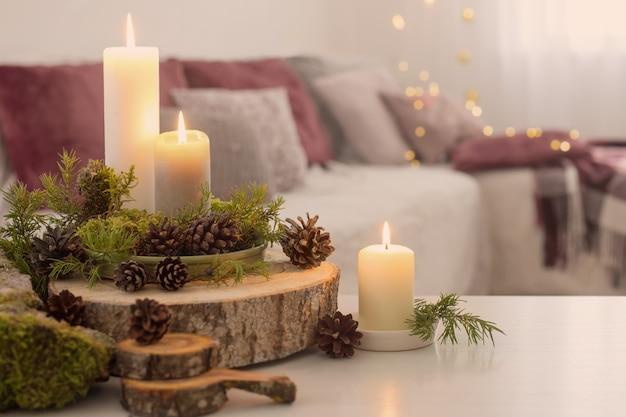 Samenstelling van kaarsen op witte tafel tegen de achtergrond van de bank thuis