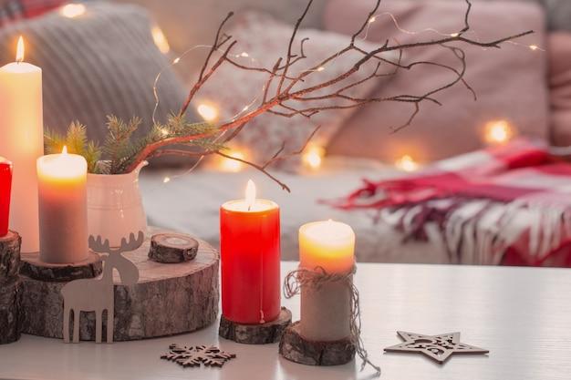 Samenstelling van kaarsen op witte tafel tegen de achtergrond van een bank met plaids en kussens. gezellig huisconcept