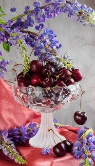 Samenstelling van kersen in een vaas, blauwe bloemen en vloeiende doek