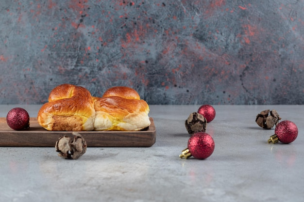 Samenstelling van kerstballen en een zoet broodje op marmeren tafel.