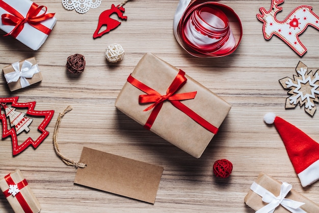 Samenstelling van kerstboomspeelgoed, linten en versierde geschenkdozen op rustieke houten tafel.