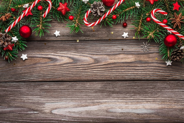 Samenstelling van kerstmis en gelukkig nieuwjaar. spar boomtakken, decoraties en snoep op houten tafel