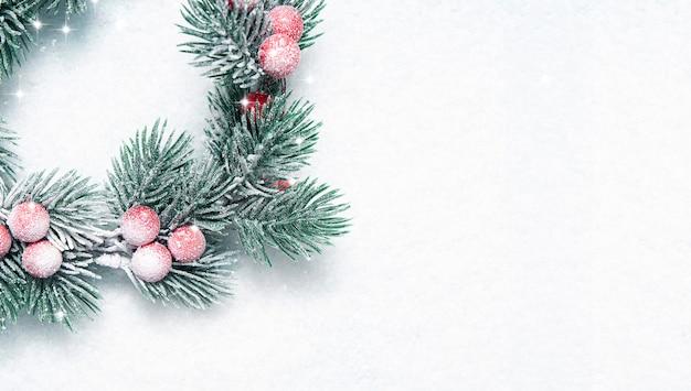 Samenstelling van kerstmis en nieuwjaar, de kroon van kerstmis met bes op sneeuw, lay-out met ruimte voor tekst