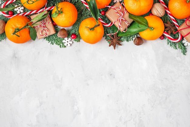 Samenstelling van kerstmis of gelukkig nieuwjaar gemaakt van mandarijnen, fir tree takken, kerstvoedselversieringen en geschenkdozen op betonnen achtergrond. plat leggen. bovenaanzicht met kopie ruimte
